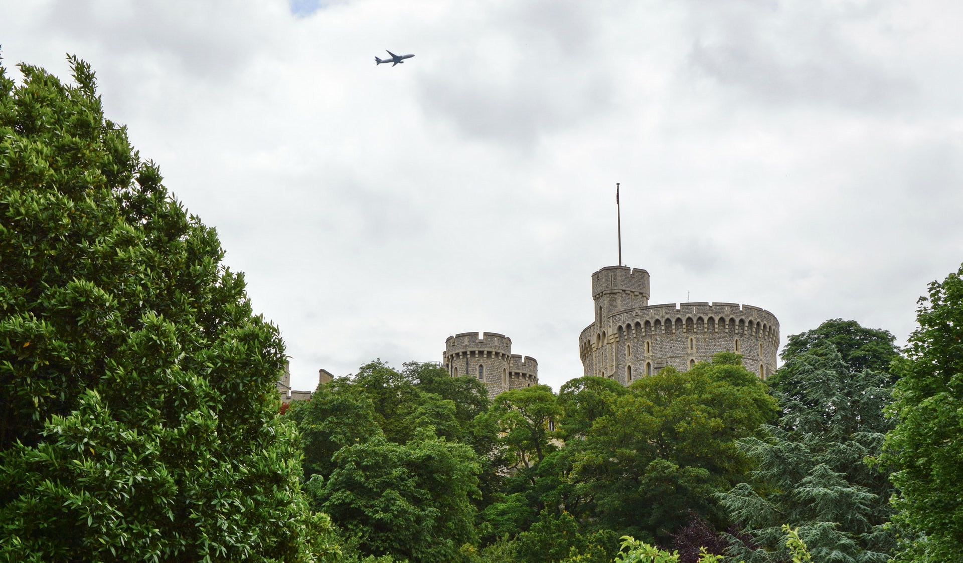 Windsor Castle is located close to Heathrow airport and often pops among trees when looking from the River Thames
